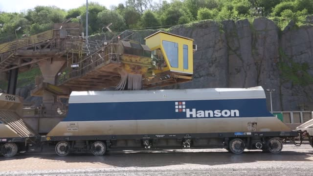 vídeos de stock e filmes b-roll de caterpillar inc 777 dump truck drives past the excavated limestone rock face at hanson brickworks whatley limestone quarry a unit of heidelberg... - caterpillar inc