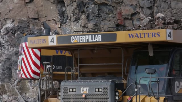 A Caterpillar Inc 777 dump truck drives past the excavated limestone rock face at Hanson Brickworks Whatley Limestone Quarry a unit of Heidelberg...
