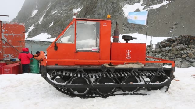 a caterpillar tracked vehicle at base orcadas which is an argentine scientific station in antarctica and the oldest of the stations in antarctica... - antarctica research stock videos & royalty-free footage