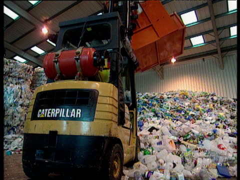 caterpillar truck in warehouse unloads plastic rubbish for recycling - bottle stock videos and b-roll footage