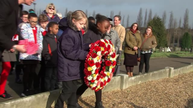 Catford school remembers WWII bombing Hither Green Cemetery EXT Two schoolgirls laying wreath at memorial to victims of Sandhurst Road School bombing