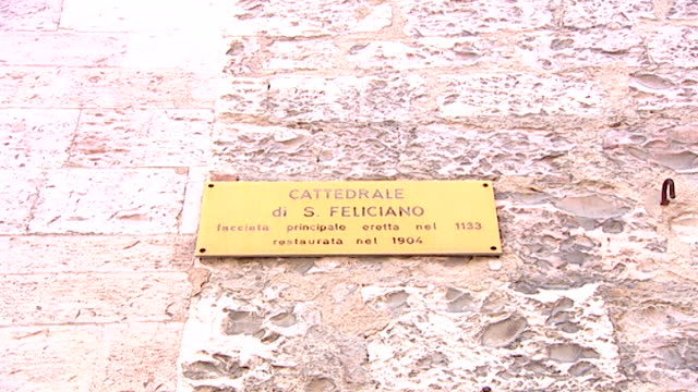 cathedral of saint feliciano. zoom-in of a sign for the cathedral of saint feliciano which reads: main facade was erected in 1133 and restored in... - zoom out 個影片檔及 b 捲影像