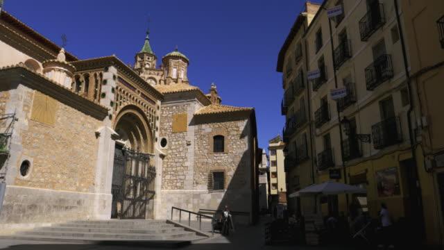 vidéos et rushes de cathedral of saint mary of mediavilla of teruel against blue sky and shadowed street cafe, teruel, aragón, spain - lieu de culte