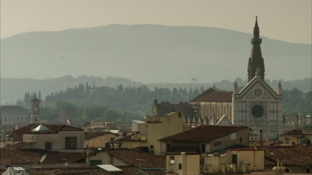 vidéos et rushes de a cathedral steeple rises above the rooftops of florence, italy. available in hd. - flèche clocher
