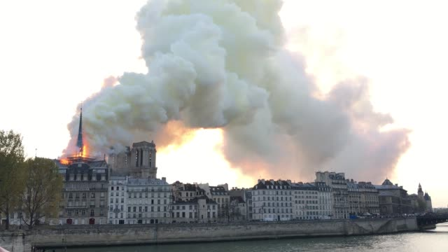 cathedrale notre dame de paris is on fire. the fire starts on the top of the xii th century monument wich is an icon of the french capital - notre dame de paris stock videos & royalty-free footage