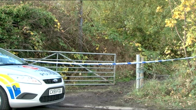 clive sharp found guilty file october 2012 north wales police car and cordoned off country lane police vans parked outside row of semidetached houses - 非常線点の映像素材/bロール