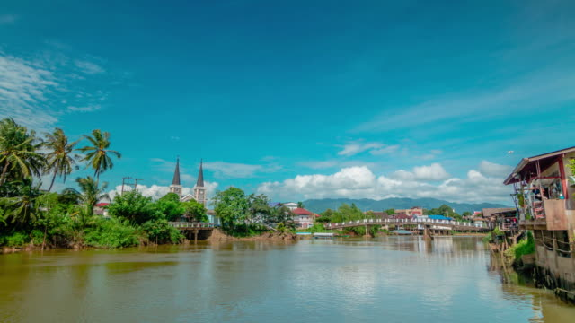 Catholic Church in Chanthaburi riverside community with clouds moving.