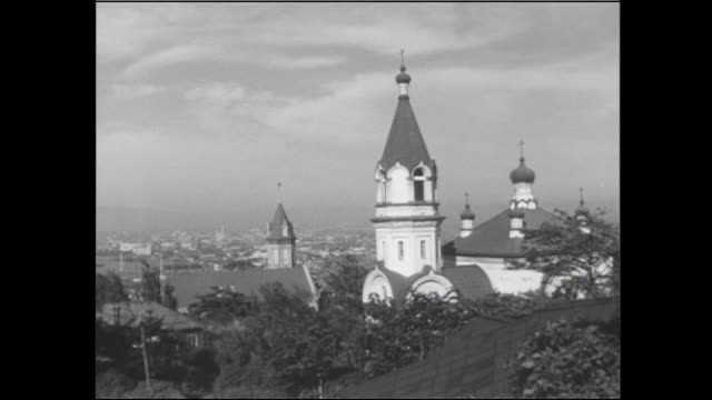 catholic church steeple towers over trees and buildings in hakodate, japan. - onion dome stock videos and b-roll footage