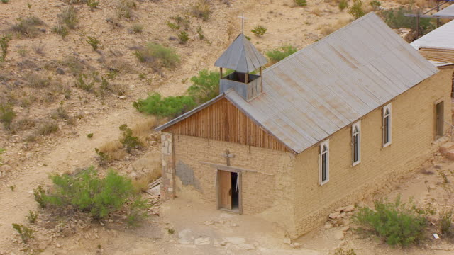 cu aerial zo catholic cross on exterior of building and town in chihuahuan desert / terlingua, texas, united states - 宗教上のシンボル点の映像素材/bロール