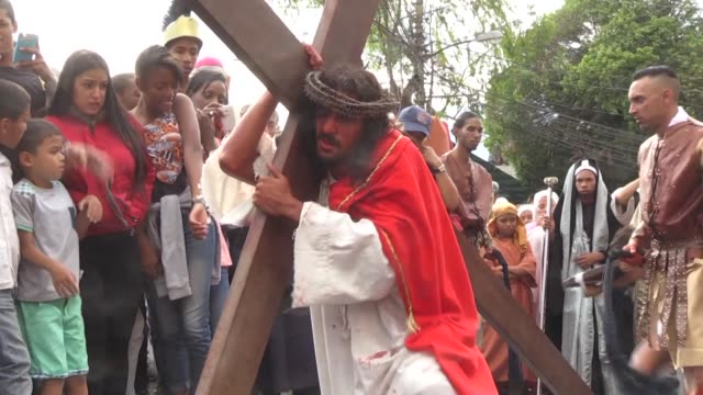 vídeos de stock, filmes e b-roll de catholic devotees re enact the crucifixion of jesus christ during a good friday procession in caracas petare neighbourhood - decretar
