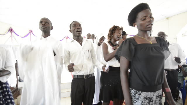 catholic easter church service at st. philip korok church, juba. pastor enos. jackie, brac worker, singing in choir. - ブラック島点の映像素材/bロール