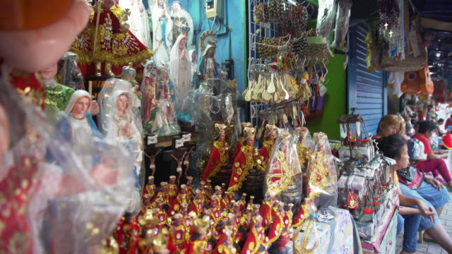 catholic figurines at street market, cebu city, philippines - ギフトショップ点の映像素材/bロール