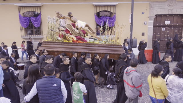 Catholic parade at Antigua Guatemala during Lent Easter celebration. Christ statue carried by people dressed in black costume.