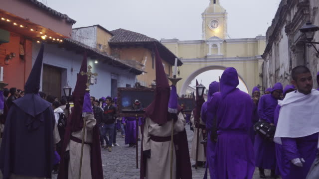 catholic parade at antigua guatemala famous street during lent / easter celebration. people dressed in purple costume and hooded crossing santa catalina arch - 四旬節点の映像素材/bロール