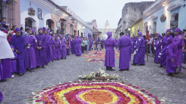 catholic parade during lent / easter at antigua guatemala famous street. multicoloured carpet and people dressed in purple costume crossing santa catalina arch. - 四旬節点の映像素材/bロール