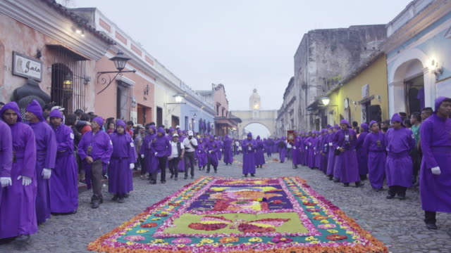catholic parade during lent / easter at antigua guatemala famous street. multicoloured carpet and people dressed in purple costume crossing santa catalina arch. - easter stock videos & royalty-free footage