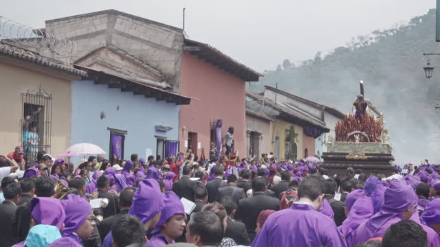 catholic parade for lent easter celebration at antigua guatemala. statue carried by people with traditional purple and black costume - 四旬節点の映像素材/bロール