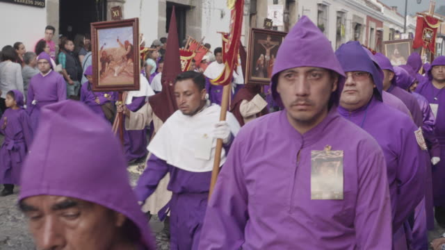 catholic parade for lent easter celebration at antigua guatemala. statue carried by people with traditional purple and hooded costume - 四旬節点の映像素材/bロール