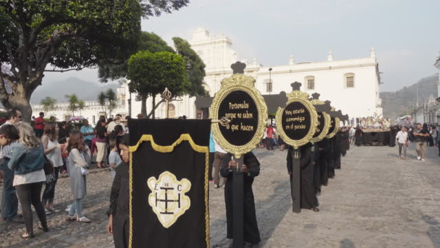 catholic parade in front of antigua guatemala cathedral during lent / easter celebration. people dressed in black costume carrying banners with bible messages. - 四旬節点の映像素材/bロール