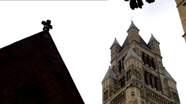 Catholic priests abused victims over course of decades Bruges Low angle shot of medieval church Statue of bearded saint Medieval rooftop with stone...