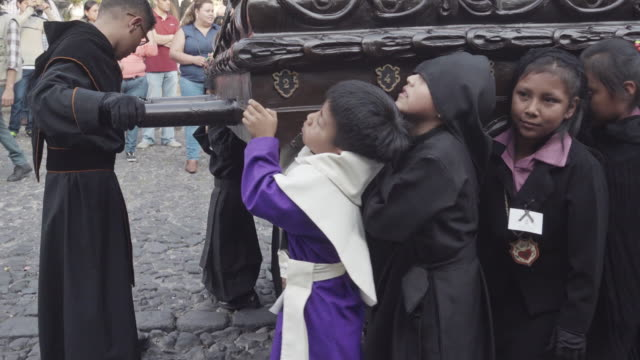 Catholic statue carried by children dressed in black costume. Lent / Easter celebration in Antigua Guatemala.