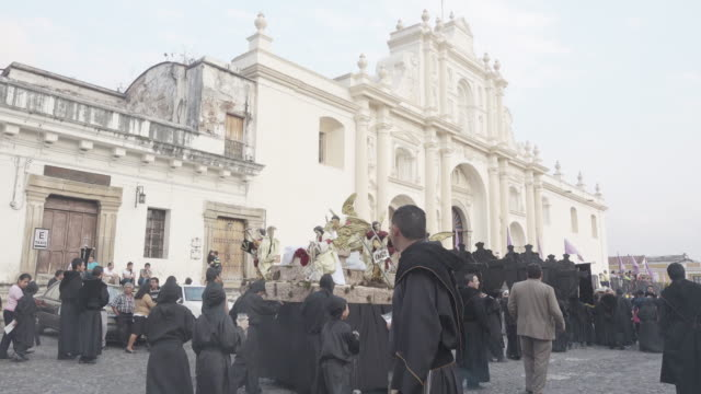 catholic statue carried by children dressed in black costume. lent / easter celebration in antigua guatemala. - guatemala stock videos & royalty-free footage
