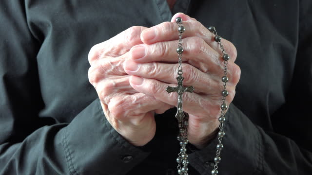 catholicism: hands of a senior woman holding a rosary and praying - prayer beads stock videos & royalty-free footage