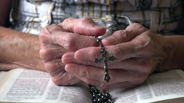 Catholicism: Hands of a senior woman holding a rosary and praying