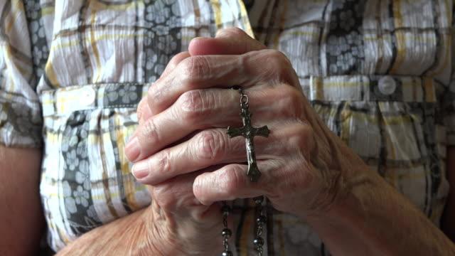 vídeos de stock, filmes e b-roll de catholicism: hands of a senior woman holding a rosary and praying - cruz objeto religioso