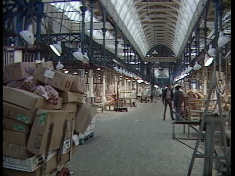 BSE Cattle disease BSE Cattle disease ITN LIB Smithfield GV Meat market arcade as traders to fro in b/g Worker pulling trolley laden with carcases RL...