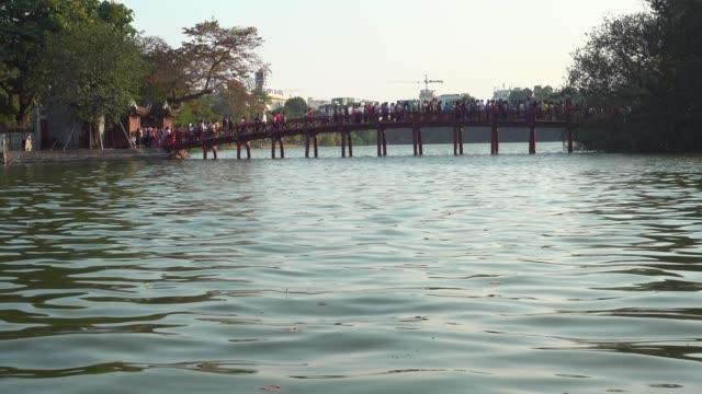 cau the huc bridge at hanoi, vietnam. crowd entering at ngoc son jade mountain buddhist temple during tet celebration. hoan kiem lake - gå tillsammans bildbanksvideor och videomaterial från bakom kulisserna
