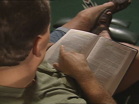caucasian adult male dressed in shorts seated in lounge chair reading bible zi cu following text line w/ right index finger o/f page repeats - bible stock videos & royalty-free footage