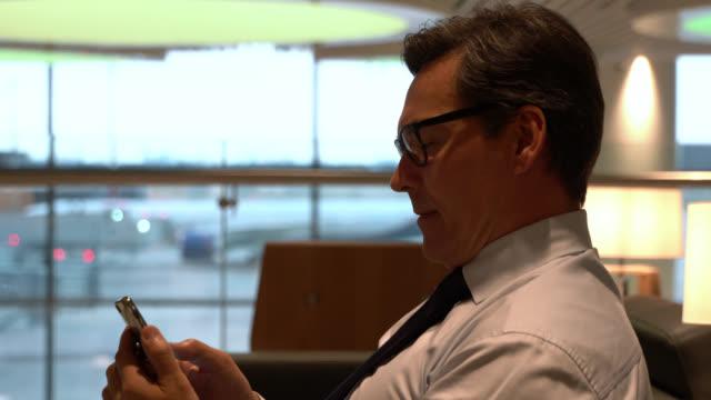kaukasischer erwachsener mann wartet am abflugbereich und schaut auf smartphone bereit, mit dem flugzeug zu reisen - wartehalle stock-videos und b-roll-filmmaterial