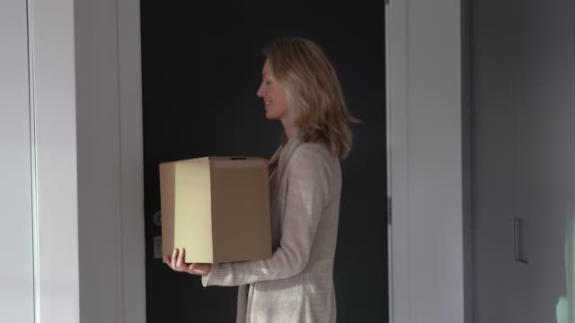 caucasian adult woman at home closing door after receiving a package looking surprised - receiving stock videos and b-roll footage