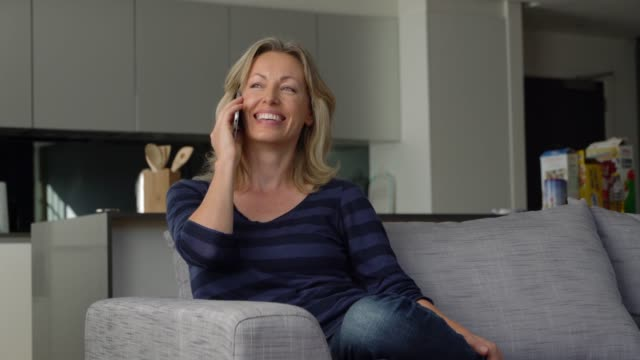 caucasian adult woman at home talking on smartphone very cheerfully - usare il telefono video stock e b–roll