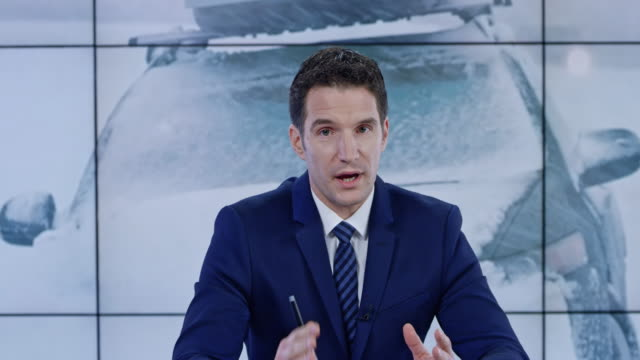 ld caucasian anchorman presenting the latest news on the severe weather conditions - mass media video stock e b–roll