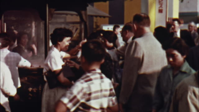 caucasian and japanese tourists anoint themselves with smoke from incense in tokyo, japan. - 1960~1969年点の映像素材/bロール