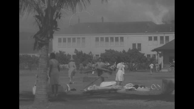 stockvideo's en b-roll-footage met ls caucasian and native hawaiian civilians scramble around on lawn of burning building during japanese attack on honolulu / pan smoke billows from... - oceanische etniciteit