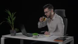 Caucasian attractive male copywriter typing text from paper on laptop and drinking tea.
