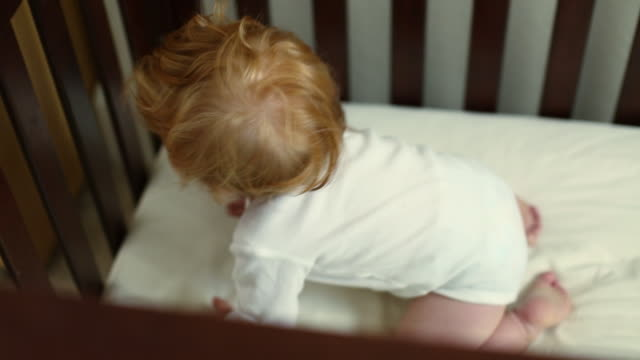 Caucasian baby boy crawling in crib then standing