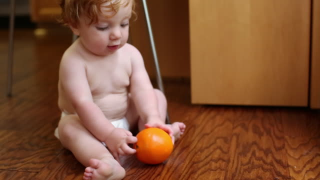 Caucasian baby boy sitting on floor playing with orange
