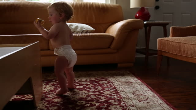 Caucasian baby boy standing and taking first steps