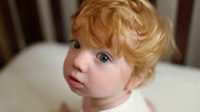 vídeos de stock, filmes e b-roll de caucasian baby boy with ruffled hair sitting in crib - cabelo assanhado