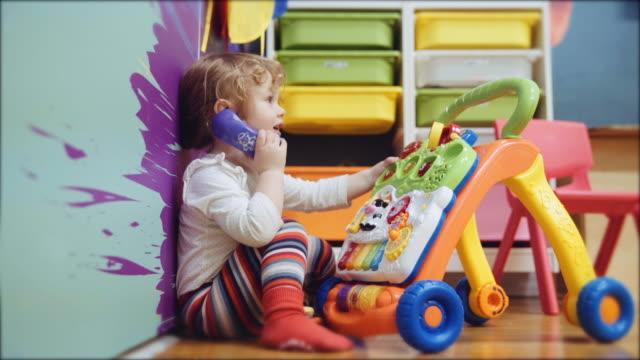 caucasian baby girl sitting on floor playing with toy telephone - 受話器点の映像素材/bロール