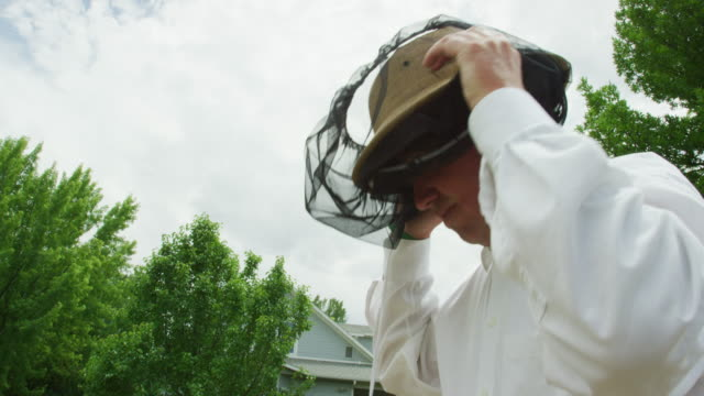 a caucasian beekeeper in his thirties puts on a beekeeping hat and veil next to beehives and a house outdoors - protective workwear stock videos & royalty-free footage