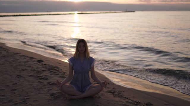 caucasian blonde woman meditates at sandy beach wearing blue summer dress during sunrise. wide panning right shot - tourist resort stock videos & royalty-free footage