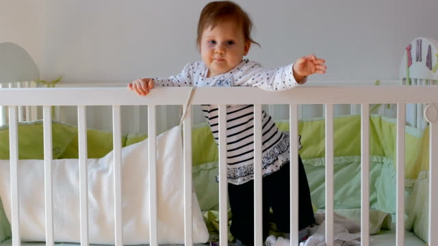 caucasian blue eyed baby girl standing for the first time on her own - crib stock videos & royalty-free footage