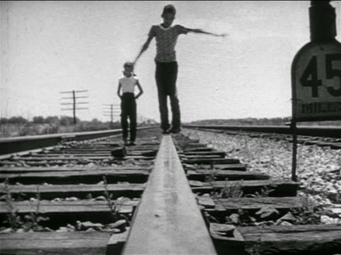 b/w 1951 caucasian boy + black girl walking on rural train tracks / louisiana / documentary - railway track stock videos & royalty-free footage