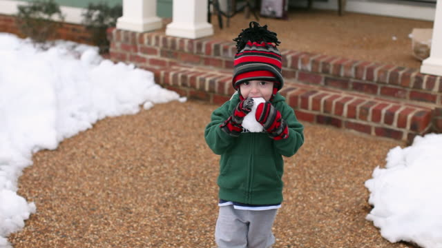caucasian boy eating snowball - mitten stock videos and b-roll footage