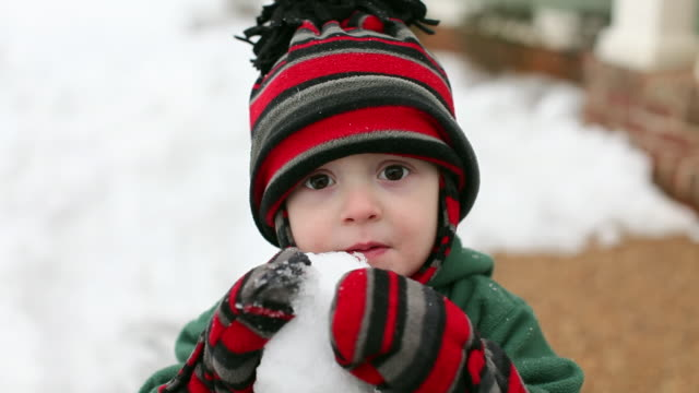 vídeos de stock, filmes e b-roll de caucasian boy eating snowball - mitten